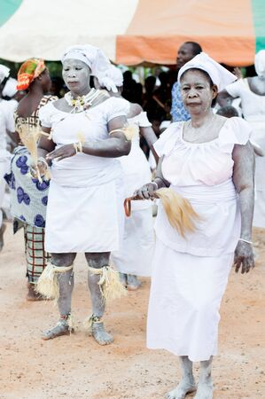 adzoped, ivory coast-august 31, 2016: two young women dressed in white powder on the body with necklaces, without ponytail shoes in hand are preparing to dance and other people standing.