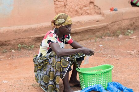 Adzop?, ivory coast - June 10, 2017: woman sitting on a stool, head tied by a scarf Imagens - 132884745