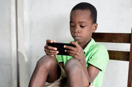 A child sitting on a chair is playing games in a mobile phone.