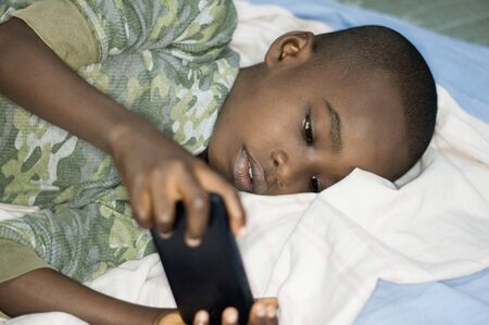 Child boy handling a mobile phone lying in bed