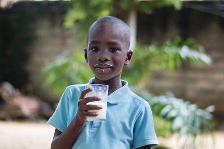 Child enjoying the taste of milk in the glass.