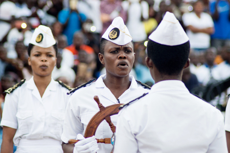 Abidjan, Ivory Coast - August 3, 2017: shoulder pad ceremony to students leaving the Maritime Academy. group of marine women dressed in white receiving a ships steering wheel as a symbol