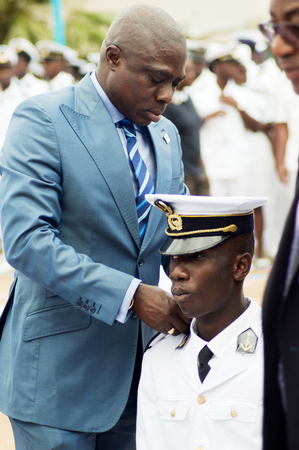 Abidjan, Cote dIvoire - August 3, 2017: ceremony of the shoulder of the students at the end of the cycle. The godfather putting the shoulders of a student kneeling