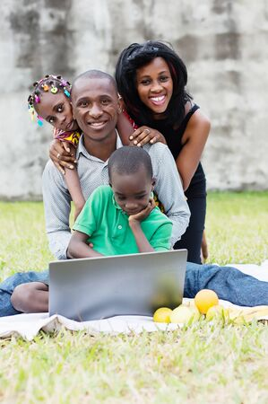 happy family sitting at the park in front of a computer and playing in a group Stockfoto - 128116846