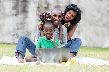 happy family sitting at the park in front of a computer and playing in a group Stockfoto - 128116848