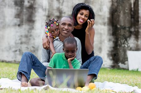 happy family sitting at the park and looking together on a laptop Stockfoto - 128116850