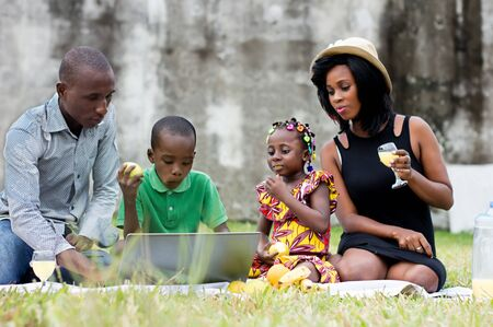 happy family with two children sitting outdoors and looking at a laptop Stockfoto - 128116852