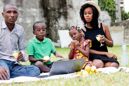 happy family with two children sitting outdoors and looking at a laptop Stockfoto - 128116847