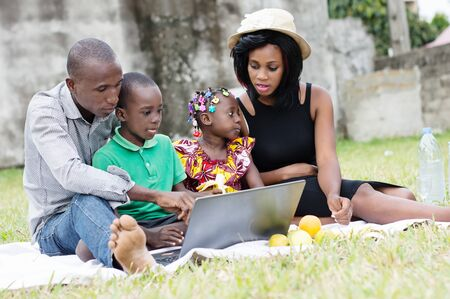Happy and modern family sitting in a park use a laptop together during their relaxation Stockfoto - 128116635