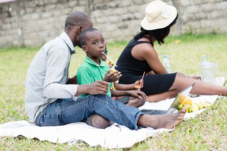 African family sitting on the lawn outside, having fun. Stockfoto - 128116638