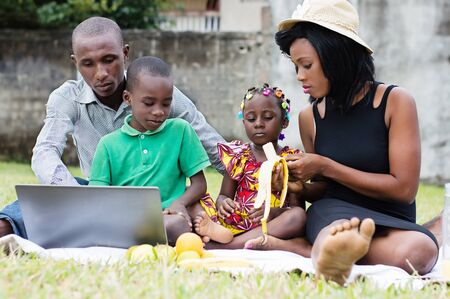 Happy and modern family sitting in the park picnic together while watching the laptop Stockfoto