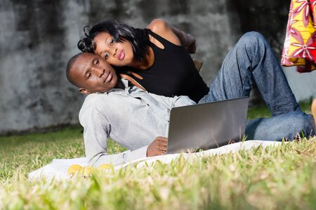 young happy couple lying in love at the park and using a laptop Stockfoto - 128116651