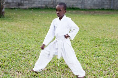 child in a kimono practicing karate alone in the garden Stockfoto - 128116657