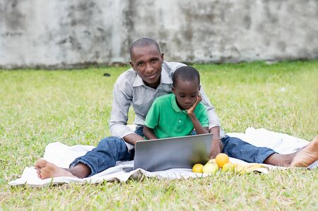 father and son sitting in the park look together on a laptop Stockfoto - 128116656