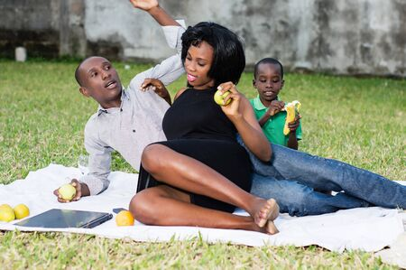 happy couple sitting at the park with their son and eating a green apple in love Stockfoto - 128116580