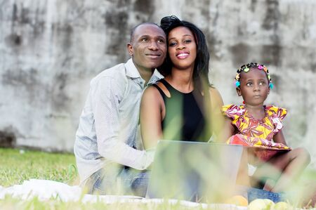 Happy family. Father, mother and child sitting in green grass