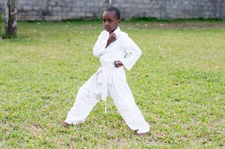 child in a kimono practicing karate alone in the garden