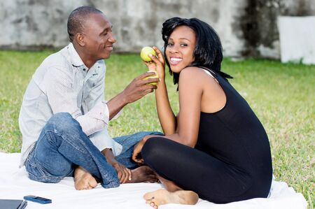 young couple sitting on the grass sharing a green apple together lovingly Stockfoto - 128116593