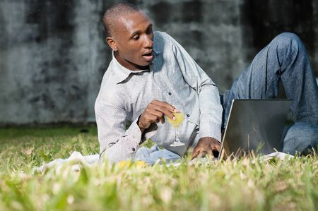 young businessman lying in the park drinks juice and works on a laptop