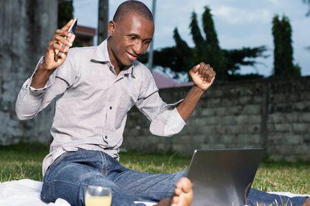 Businessman sitting in garden looking joyfully at his laptop Stockfoto - 128116594