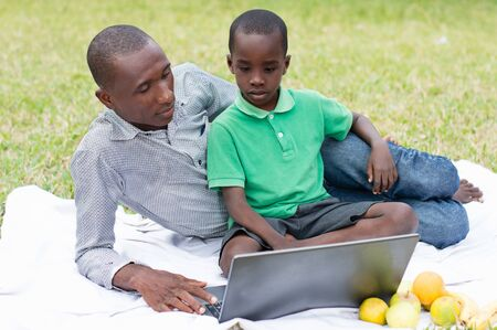 father and son sitting in the park look together on a laptop Stockfoto - 128116597