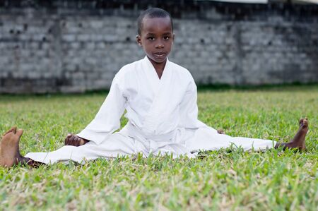 Little boy fighting in karate outfit sitting and showing martial art gesture in the park Stockfoto - 128116602