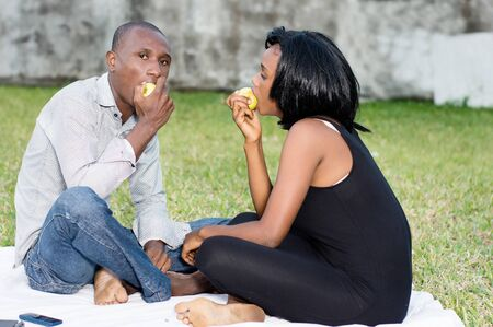 young couple sitting on the grass eating a green apple together Stockfoto