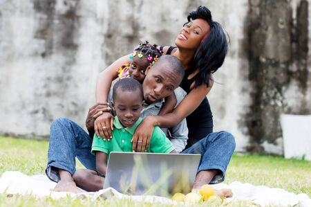 portrait of a family sitting at the park playing together in front of a computer Stockfoto - 128116603