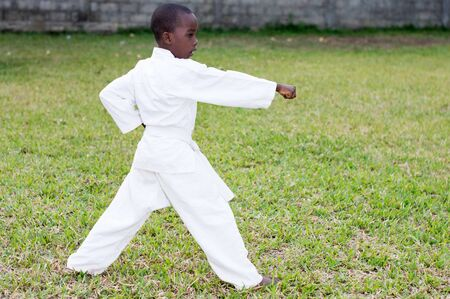 profile of a young boy in a kimono practicing karate alone in the park Imagens