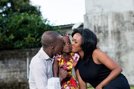 father and mother cheerfully kisses their daughter tenderly in the park Stockfoto