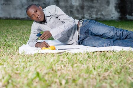 Young man lying in the park and using his mobile phone during a picnic Stockfoto