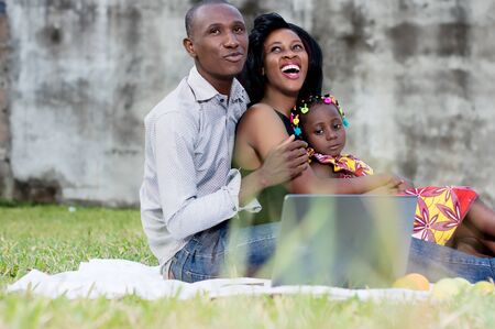 merry father and mother sitting in park with their daughter in their arms Stockfoto