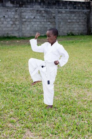 young boy alone in the park in kimono practice martial arts