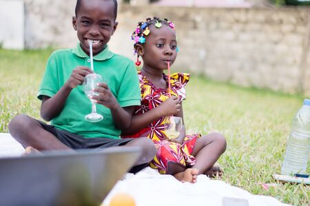 two happy children sitting at the park in front of a laptop and drinking juice Stockfoto - 128116259
