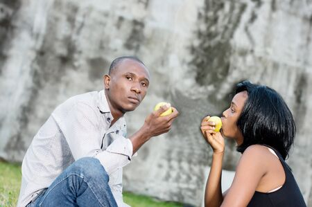 happy young couple at the park sitting entwined and sharing a green apple Stockfoto - 128116263