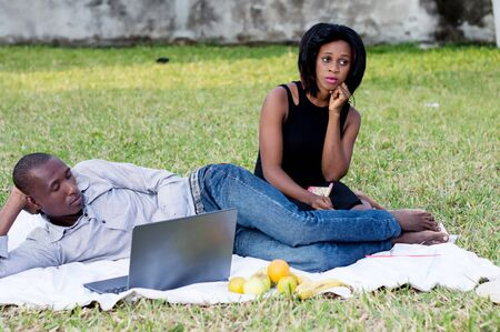 young couple sitting in the park sad and do not talk after a dispute