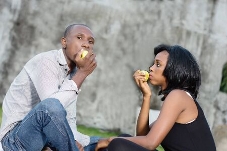 happy young couple at the park sitting entwined and sharing a green apple Stockfoto - 128116268