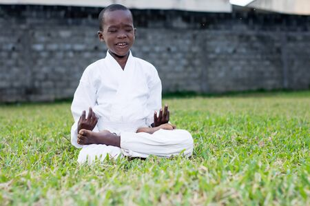 Cute child in white kimono sitting in garden pondering eyes closed Stockfoto - 128116272