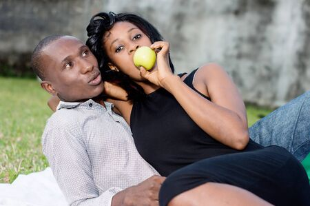 young couple sitting on the grass eating a green apple together Stockfoto - 128116274