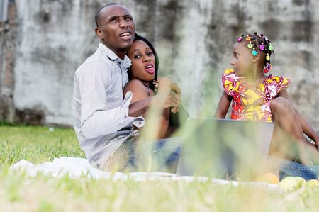 Happy family. Father, mother and child sitting in green grass Stockfoto - 128116279