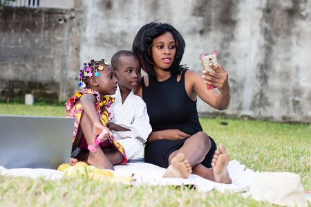 young mother takes photos with her children in the park