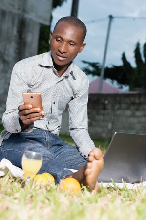 Portrait of a young businessman sitting at the park in front of laptop and looking surprised on a mobile phone