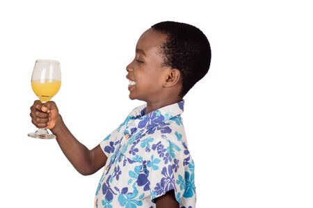 Happy child holding a glass of fruit juice isolated on white background. Stockfoto - 128116031