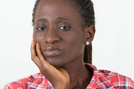 Close-up of young woman with hand on cheek suffering from tooth pain