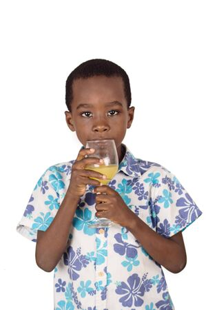 Little boy drinking orange juice in a clear glass while watching the camera.