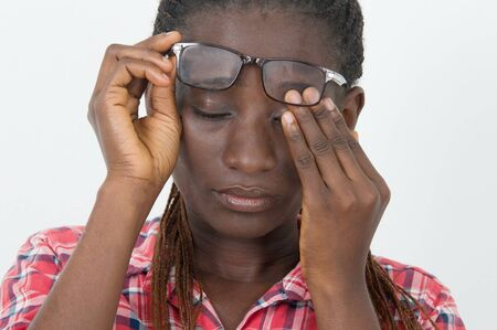 Tired woman with vision problems, glasses and suffering from headache or migraine, Stockfoto