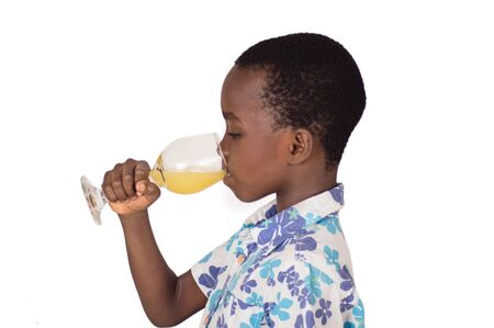 Small boy concentrated to drink orange juice in a clear glass.