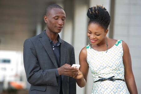 young business people standing out side by side sharing information on a mobile phone. Stockfoto
