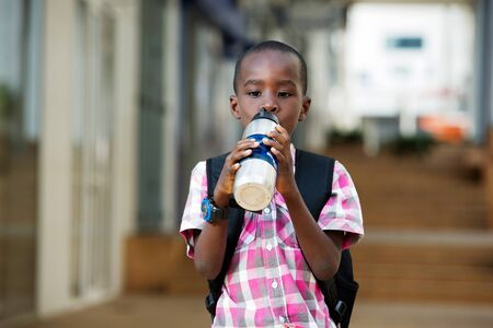little boy backpack drinks water in his gourd on the road to school.
