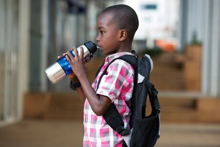 small schoolboy with a backpack, standing drinks water in a bottle on the way down the class. Stockfoto